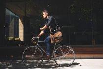 Joven hombre de negocios comprobando el tiempo mientras pedalea en oficinas - foto de stock