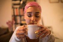 Стильная женщина пьет кофе дома — стоковое фото
