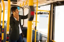 Young businessman talking on mobile phone while travelling in bus — Stock Photo