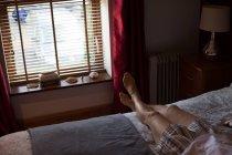 Mujer con las piernas cruzadas en el tobillo en el dormitorio en casa - foto de stock