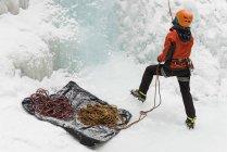 Задній вид жіночий скелелаз проведення каната взимку — стокове фото