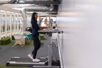 Female executive talking on mobile phone while exercising on treadmill in office — Stock Photo