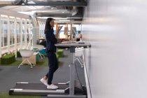 Weibliche Führungskraft telefonieren mit Handy während dem Training auf dem Laufband im Büro — Stockfoto