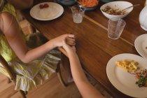 Mutter an Hand ihrer Tochter während dem Mittagessen in der Küche zu Hause — Stockfoto