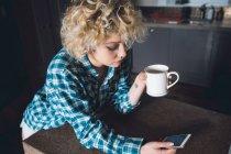 Mulher tomando café durante o uso do telefone móvel na cozinha em casa — Fotografia de Stock