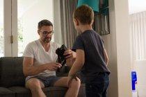 Père avec son fils tenant le casque de réalité virtuelle dans la salle de séjour à la maison — Photo de stock