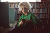 Giovane donna che utilizza il telefono cellulare in biblioteca — Foto stock