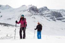 Пара стоячи на на снігу capped гори взимку — стокове фото