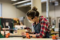 Young female carpenter working in workshop — Stock Photo