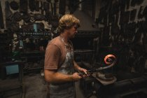 Blacksmith shaping a metal rod in workshop — Stock Photo