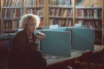 Junge Frau telefoniert in Bibliothek — Stockfoto