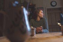 Nachdenkliche Frau mit Kaffee zu Hause — Stockfoto