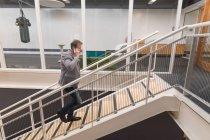 Підприємець говорити на мобільному телефоні під час прогулянки нагорі в офісі — стокове фото