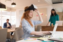 Female graphic designer with virtual reality headset using laptop in office — Stock Photo