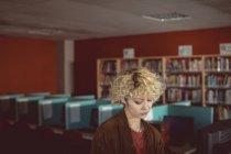 Gentil jeune femme debout dans la bibliothèque — Photo de stock