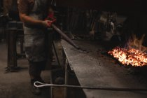 Blacksmith heating metal rod in fire at workshop — Stock Photo