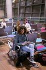 Женщина, используя мобильный телефон в зоне ожидания в аэропорту — стоковое фото