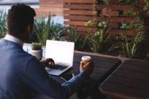 Empresario tomando café mientras usa laptop en cafetería en la oficina - foto de stock