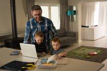 Padre e i suoi figli con il computer portatile a casa — Foto stock