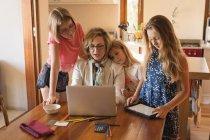 Madre e hijas usando portátil y tableta digital en casa - foto de stock