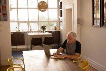 Homme senior actif, écrire sur un journal à la maison — Photo de stock