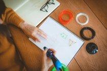 Средняя секция женщины рисует скетч в книге дома — стоковое фото