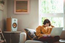 Mujer utilizando la computadora portátil en la sala de estar en casa - foto de stock