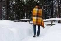 Задній вид людини загорнутий у ковдру ходьба протягом зими — стокове фото