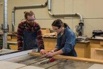 Mâles et femelles charpentiers travaillent ensemble à l'atelier — Photo de stock