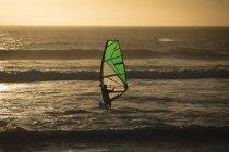 Surfista maschio surf con tavola da surf e kite Beach — Foto stock