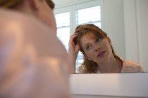 Женщина смотрит на зеркало в ванной комнате дома — стоковое фото