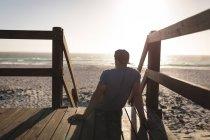 Surfeur masculin se relaxant sur la tour de guet à la plage au crépuscule — Photo de stock