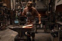 Blacksmith hammering a hot metal rod in workshop — Stock Photo