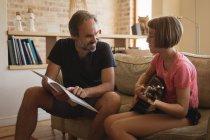 Padre che aiuta la figlia a suonare la chitarra nel salotto — Foto stock