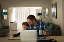 Father helping son with his homework at home — Stock Photo