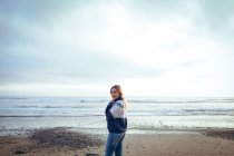 Porträt einer Frau, die in der Abenddämmerung am Strand steht — Stockfoto