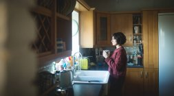 Mulher atenciosa tomando café na cozinha em casa — Fotografia de Stock