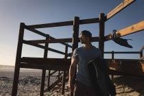 Продуманий чоловічого серфер, стоячи на пляжі — стокове фото