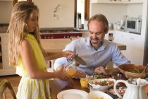 Daughter serving juice to her father in kitchen at home — Stock Photo