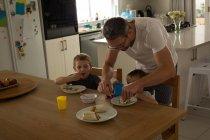 Père et fils, un petit déjeuner sur une table à manger à la maison — Photo de stock