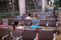 Frau mit Handy im Wartebereich am Flughafen — Stockfoto