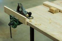 Wagenheber mit Holzstück auf einem Tisch in der Werkstatt — Stockfoto