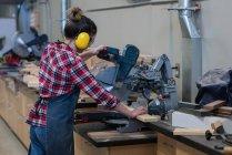 Menuisier femelle utilisant la machine de découpe de meuleuse à l'atelier — Photo de stock
