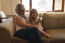 Mother and daughter sitting together in living room at home — Stock Photo