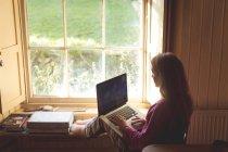 Woman using laptop near window at home — Stock Photo
