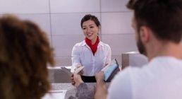Stewardess interagiert mit Pendlern am Schalter im Flughafen — Stockfoto
