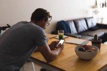 Uomo che utilizza il telefono cellulare in soggiorno a casa — Foto stock