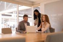 Geschäftskollegen diskutieren über Laptop im Konferenzraum im Büro — Stockfoto