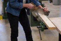 Средняя часть женского плотника с помощью ручной пилы в мастерской — стоковое фото