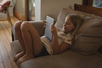 Fille détendue à l'aide de tablette numérique dans la salle de séjour à la maison — Photo de stock